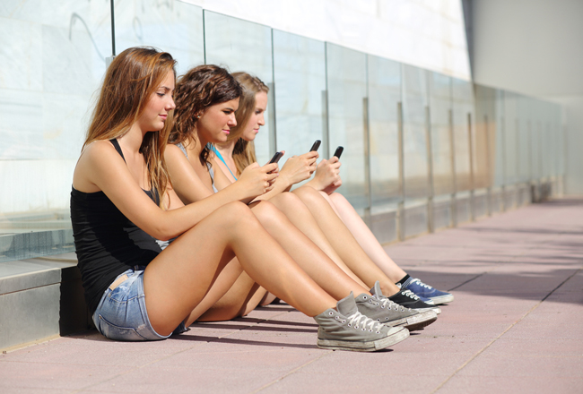Group-of-three-teenager-girls-on-their-phones